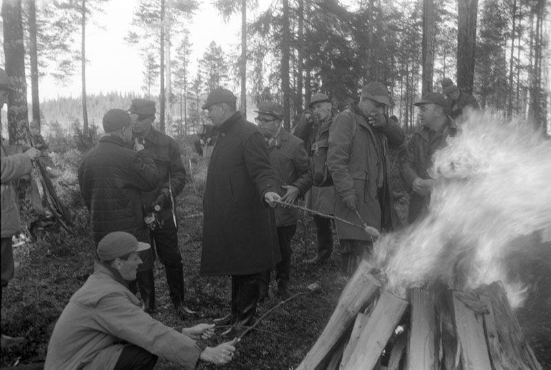Korvgrillning ute i skogen under en paus i älgjakten, november 1965. Fotograf: Rafael Olin. SLS/Rafael Olins samling (ÖTA 112)